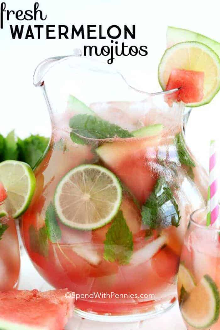 A pitcher of Fresh Watermelon Mojitos garnished with watermelon and lime