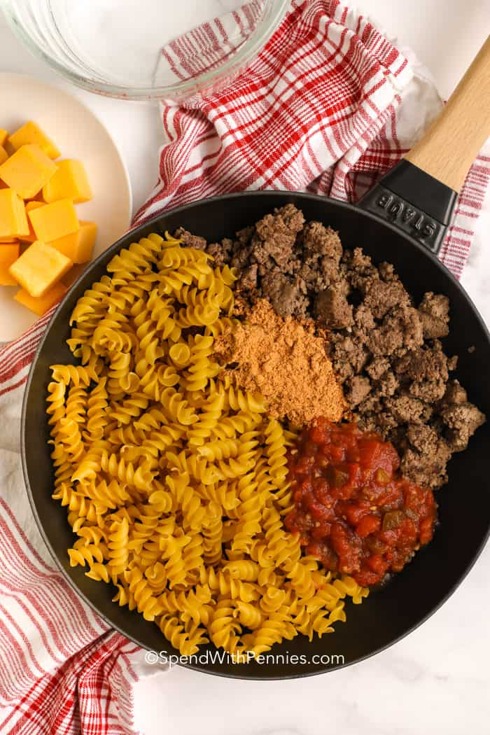 Combining meat and taco seasoning with pasta in a skillet