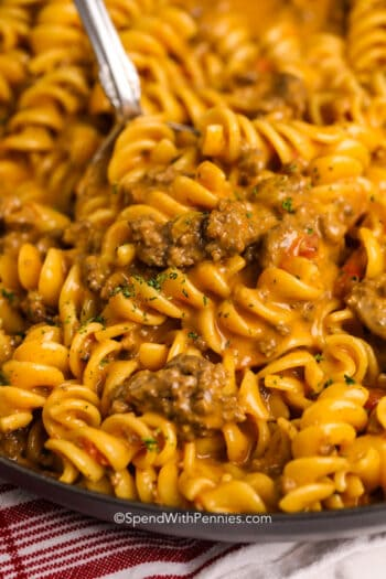 Cheesy taco pasta in a pan with a serving spoon