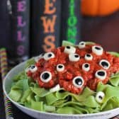 green pasta with tomato sauce and cheese and olive eyeballs