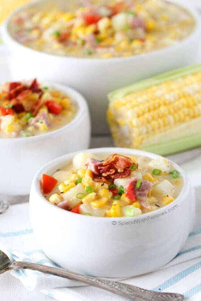 Two white bowls of Ham and Corn Chowder with an ear of corn and a bigger bowl of it in the background