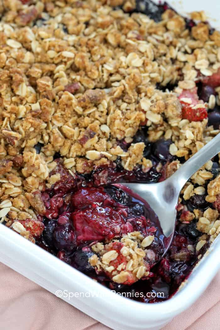 Mixed Berry Crisp in a baking dish with serving spoon