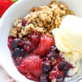 Mixed Berry Crisp in a white bowl with ice cream