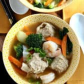 Two bowls of wonton soup with shrimp and vegetables