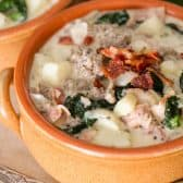 Zuppa Toscana with bacon on top in an orange bowl