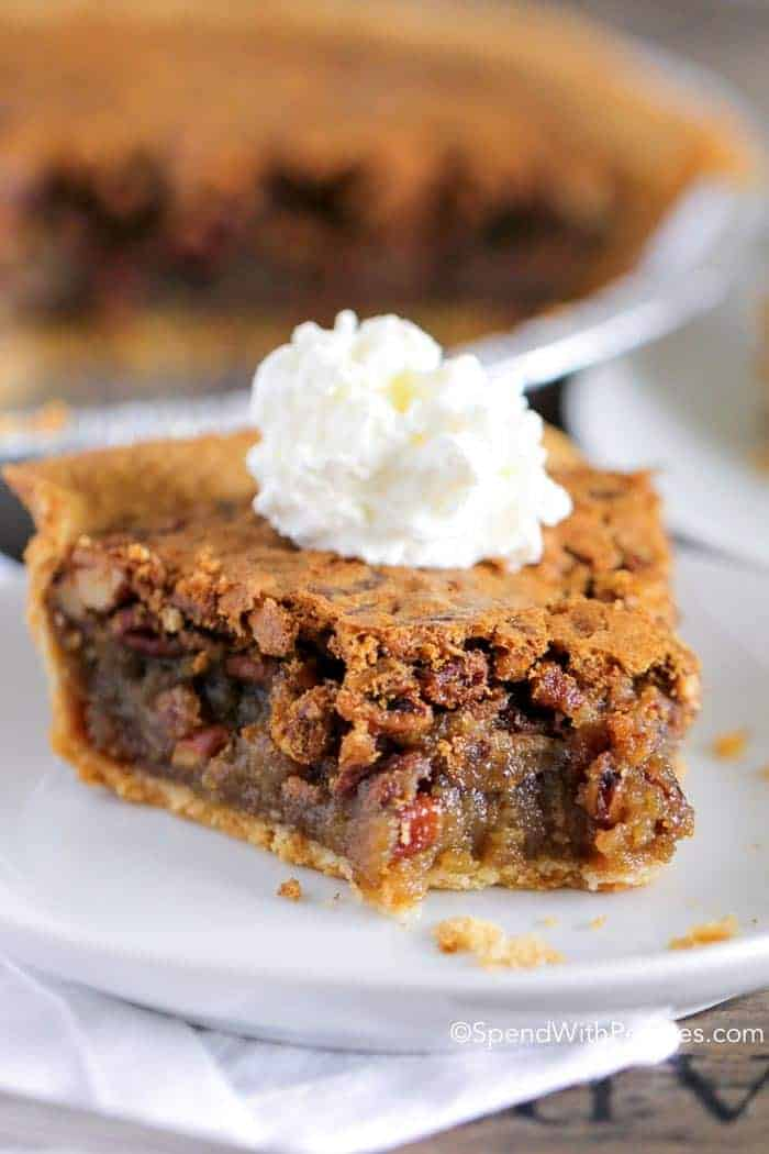 Slice of pecan pie with whipped cream on top on a white plate