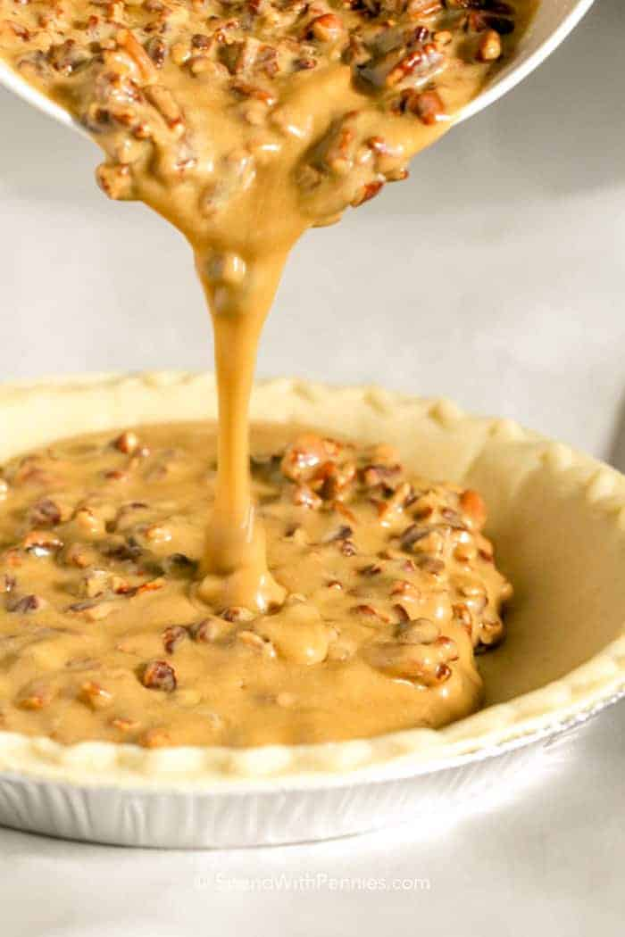 Pouring the Easy Pecan Pie filling into a pie shell