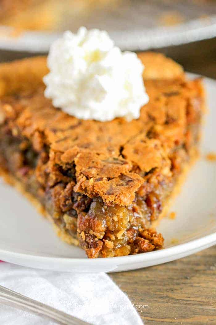 A piece of this easy Pecan pie recipe made with brown sugar instead of corn syrup and served on a white plate