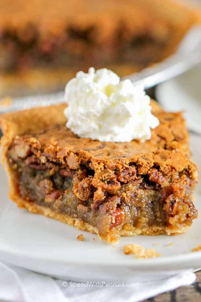 Pecan Pie on a plate with whipped cream made from an easy recipe.