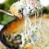 Cheesy Ranch Spinach Dip with a cheesy scoop being lifted out