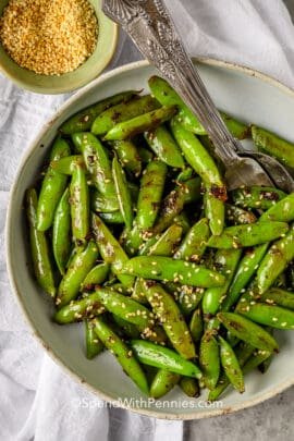 snap peas garnished with sesame seeds in a bowl with a fork and spoon