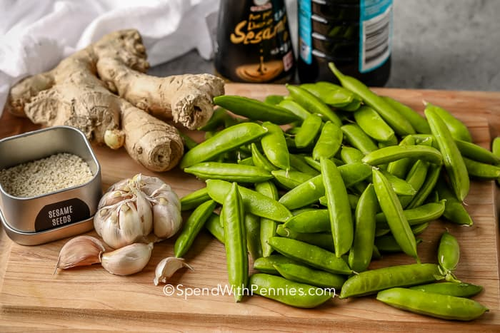 snap peas, garlic, ginger and seasonings on a wood cutting board