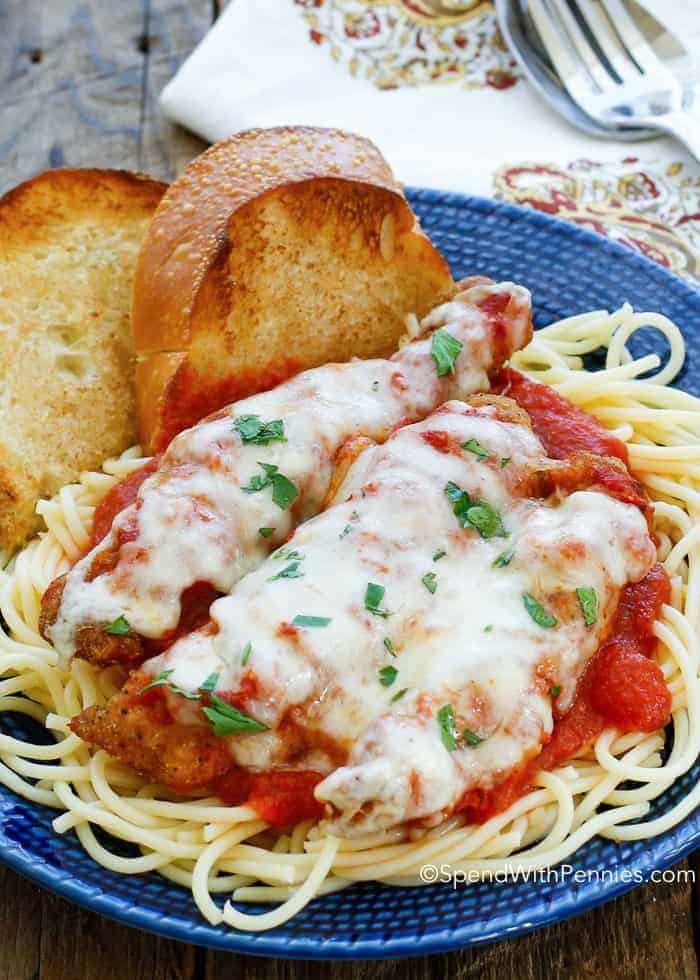 Chicken parmesan on a bed of spaghetti with a side of garlic bread