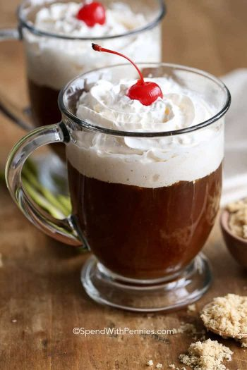 Irish coffee in a clear mug topped with whipped cream and cherry