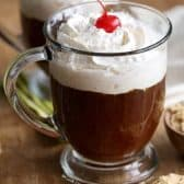 two mugs of Irish Coffee topped with whipped cream and cherries