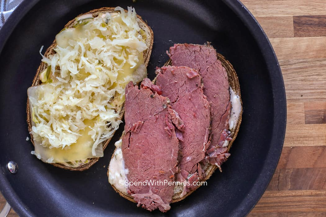 Ingredients of a reuben sandwich being fried on bread like corned beef and sauerkraut.