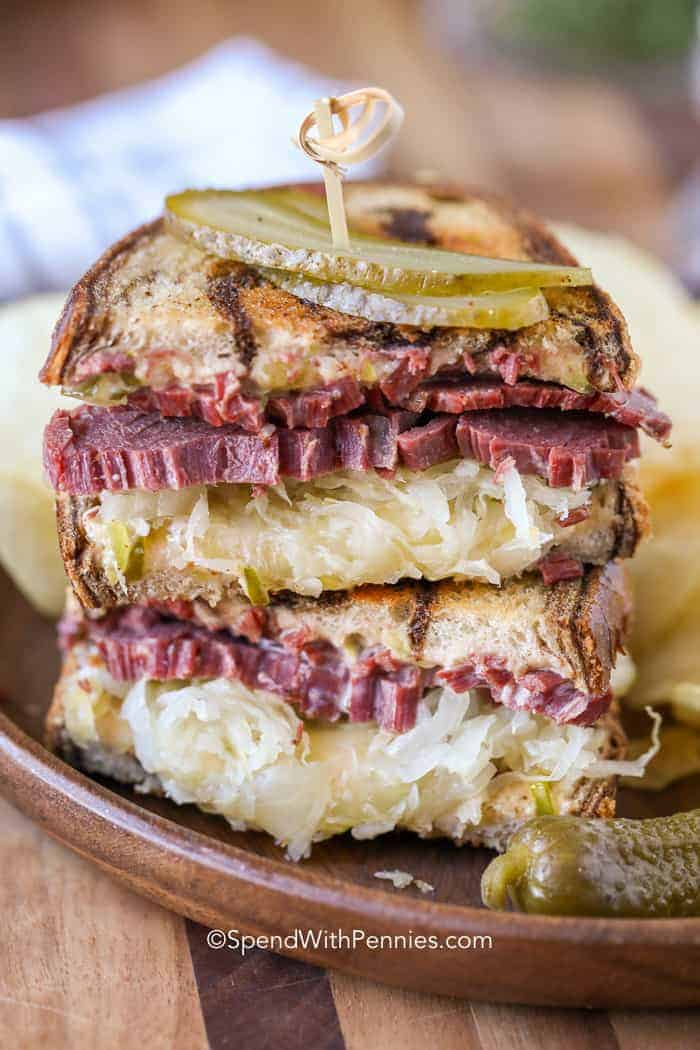 Reuben Sandwiches on a plate with sauerkraut and pickle slices