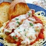 A bowl of chicken parmesan over spaghetti