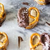 Easy Cookie Dough Pretzel Bites -- The perfect combination of sweet & salty! These no bake treats will be the first thing gone from your snack table! Egg-free cookie dough sandwiched between pretzels and dipped in dark chocolate!
