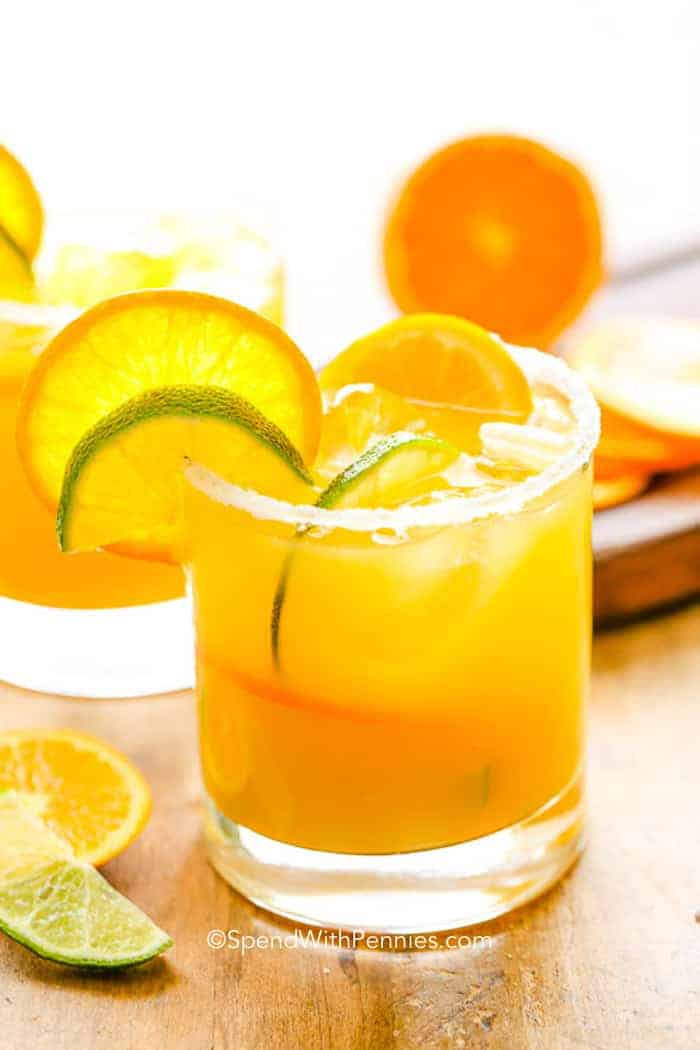 Orange margarita in a glass with lime and orange slices.