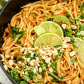 Peanut Thai noodles in a pot with peanut cilantro and lime wedges on top