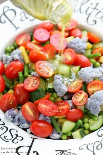 Drizzling dressing over Farmers' Market Tortellini Salad