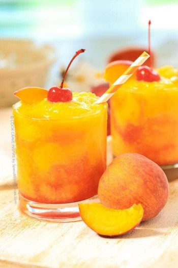 Glasses of Frozen Peach Champagne Cocktail surrounded by peaches