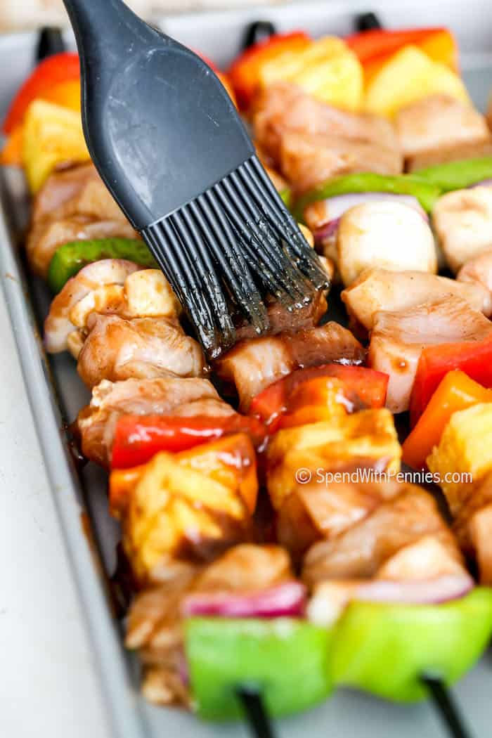 hawaiian chicken kabobs being brushed with marinade