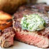 Steak on a plate with herbed butter on top