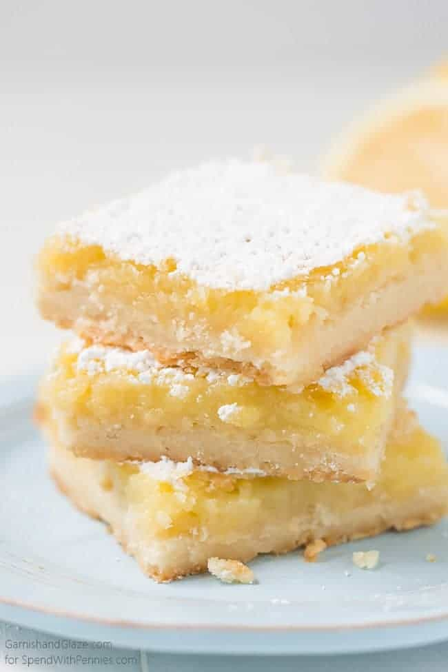 A stack of 3 lemon bars on a light blue plate.