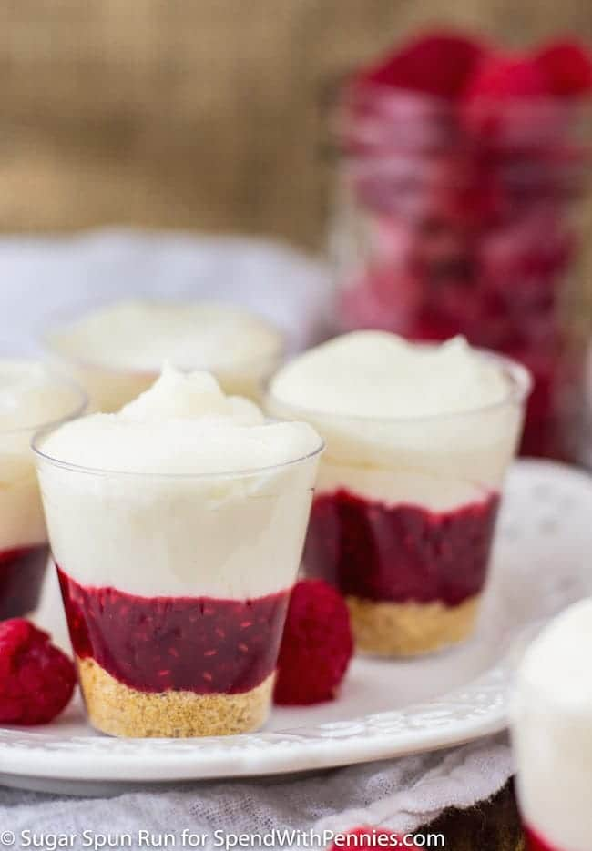 Easy, no-bake Raspberry Cheesecake Dessert Shooters! Beautiful little cups of tart raspberry filling topped with a rich, creamy, no-bake cheesecake.