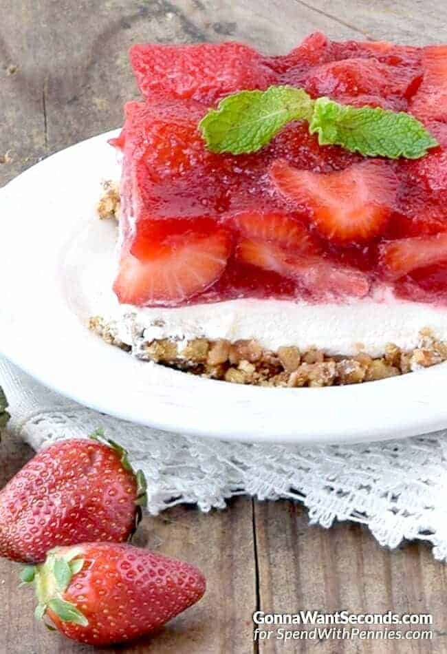 Strawberry Pretzel Salad on a white plate with two strawberries