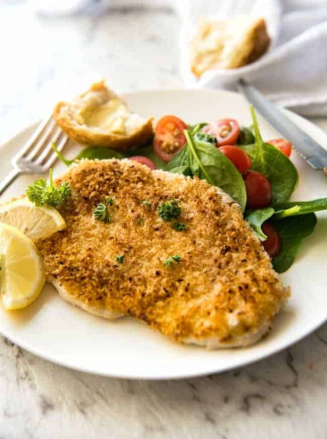 Chicken Schnitzel on a white plate with a salad and lemon wedge
