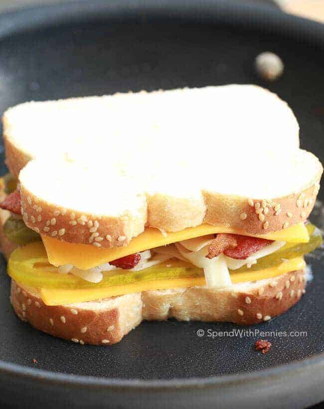 Uncooked bacon grilled cheese with pickles on skillet