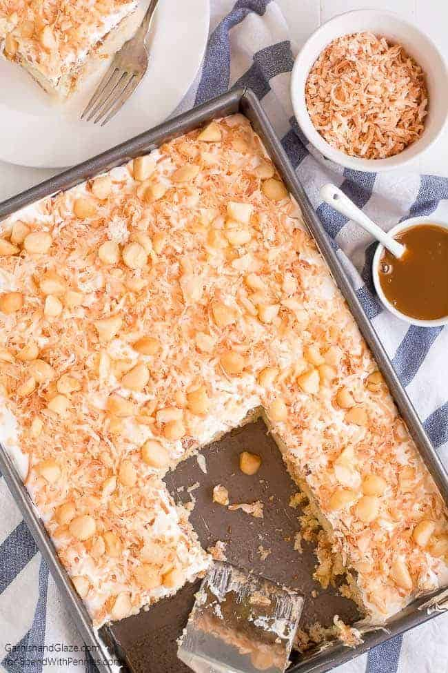 Overhead shot of Coconut Caramel Poke Cake ina baking sheet with a few slices removed from it
