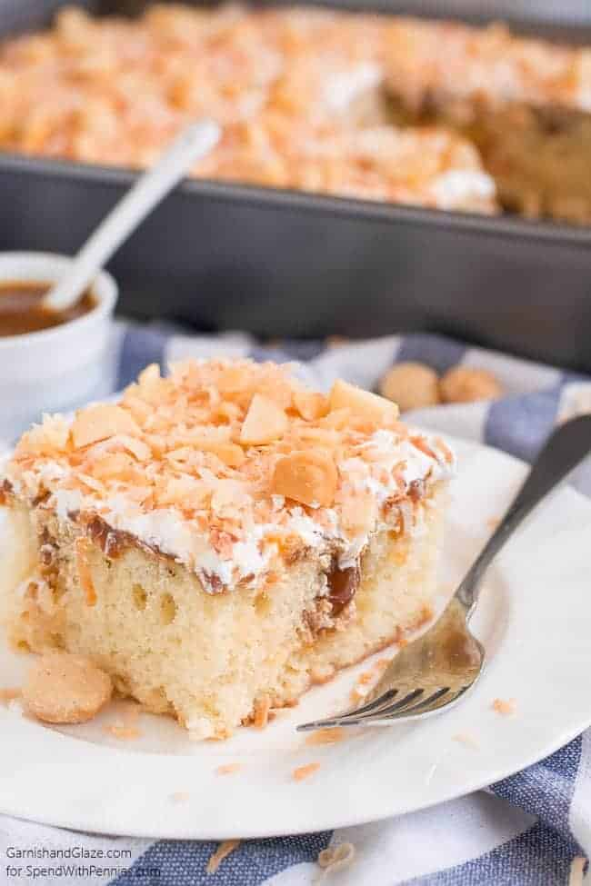Coconut Caramel Poke Cake on a white plate with a fork next to it