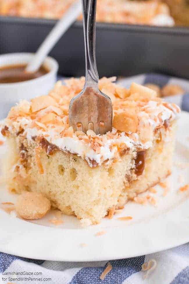 Coconut Caramel Poke Cake on a white plate with fork sticking out of it