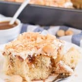 Slice of Coconut Caramel Poke Cake on a white plate with a baking dish of it in the background