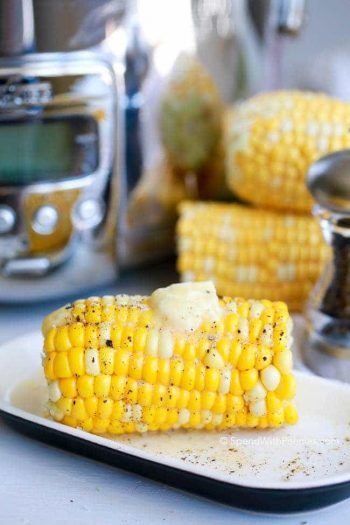 Corn on the cob with butter on top, on a dish with a slow cooker and two ears of corn in the background