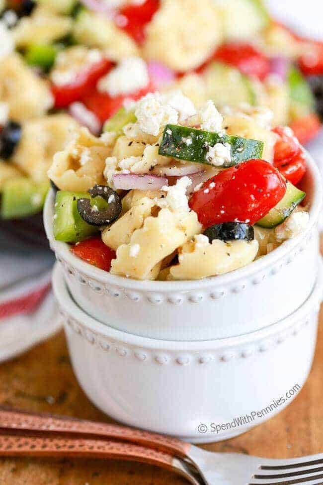 Small white dish of Greek Tortellini Salad with two forks in front of it