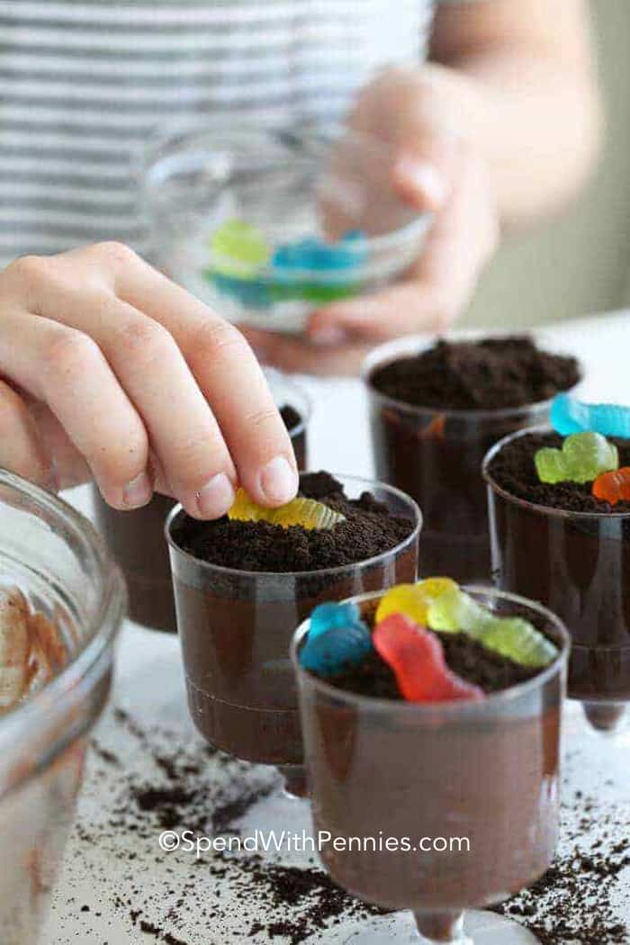 Gummy worms being places on top of the Oreo Dirt Cups.