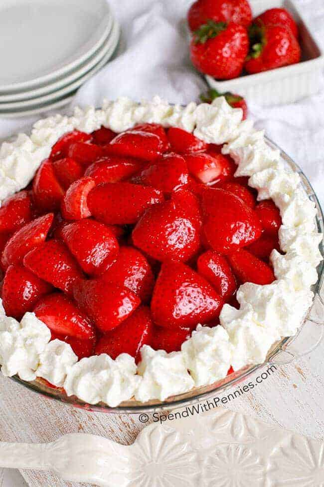 A whole Strawberry Cheesecake Pie with whipped cream and a stack of plates.
