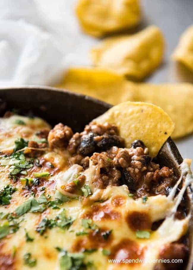 Close up on Beef Enchilada Dip showing melted cheese and chips