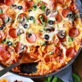 Overhead shot of Pizza Tortellini Bake in black pan with serving spoon in it