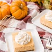 Two square white plates with a A Pumpkin amaretto cheesecake bar on them, on a table with red plaid tablecloth along with a fork, whisk and pumpkins