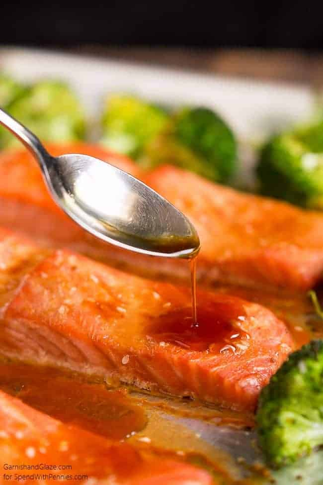 a metal spoon pouring sauce onto Sesame Ginger Salmon and Broccoli with broccoli in the background