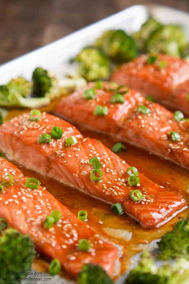 Close up of One Pan Sesame Ginger Salmon pieces with green onion garnish and broccoli on a sheet pan