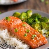 One Pan Sesame Ginger Salmon on a grey plate, over rice and a side of broccoli