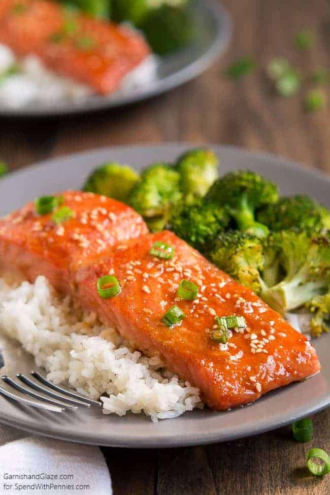 One Pan Sesame Ginger Salmon and Broccoli with green onion garnish and rice on a plate with a fork