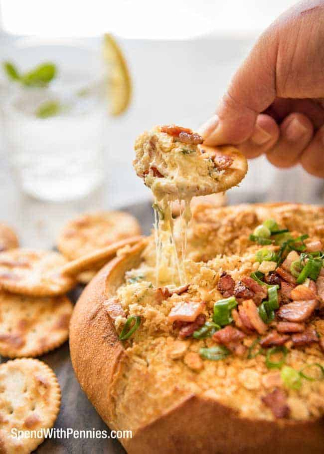 scooping Warm Bacon Cheese Dip with cream cheese, bacon and cheddar and served in a bread bowl